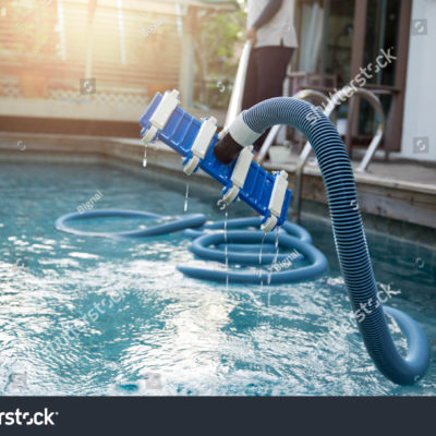 stock-photo-man-cleaning-swimming-pool-with-vacuum-tube-cleaner-early-in-the-morning-520037560